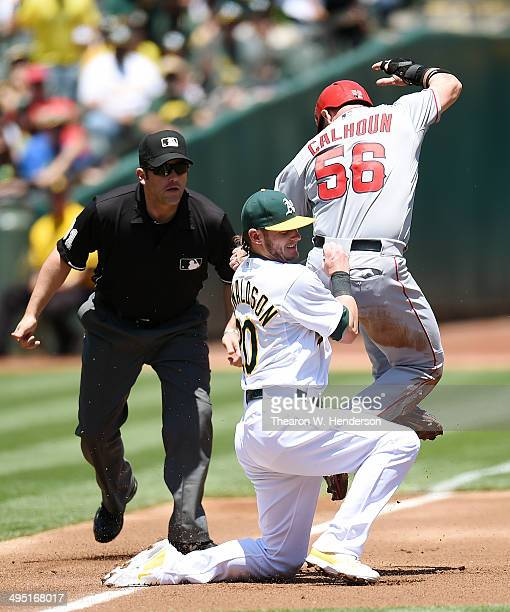 Kole Calhoun of the Los Angeles Angels of Anaheim gets tagged out at third base by Josh Donaldson of the Oakland Athletics in the top of the first...