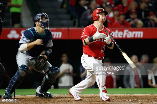 Kole Calhoun of the Los Angeles Angels of Anaheim hits a tworun homerun as Mike Zunino of the Seattle Mariners looks on during the seventh inning of...
