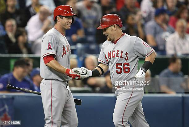 Kole Calhoun of the Los Angeles Angels of Anaheim is congratulated by David Freese after hitting a solo home run in the fourth inning during MLB game...