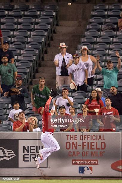 Kole Calhoun of the Los Angeles Angels of Anaheim leaps to make a catch to rob Kyle Seager of the Seattle Mariners of a tworun home run during the...