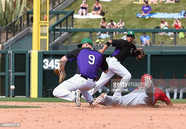 Kole Calhoun of the Los Angeles Angels of Anaheim steals second base as DJ LeMahieu of the Colorado Rockies fields the throw from home plate during...