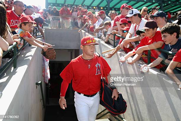Kole Calhoun of the Los Angeles Angels of Anaheim walks out onto the field past fans before the spring training game against the San Francisco Giants...