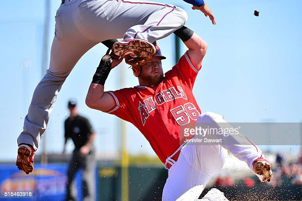Kole Calhoun of the Los Angeles Angels safely slides under Joey Gallo of the Texas Rangers in the second inning of the spring training game at Tempe...