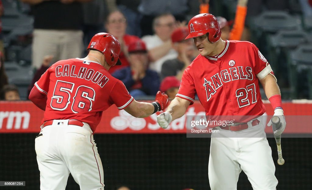 Kole Clhoun #56 of the Los Angeles Angels of Anaheim is greeted by on deck batter Mike Trout #27 as he returns to the dugout after hitting a solo home run in the fifth inning against the Seattle Mariners on September 30, 2017 at Angel Stadium of Anaheim in Anaheim, California.