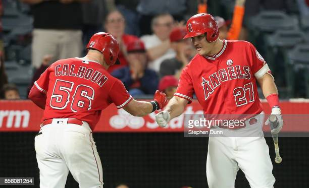 Kole Clhoun of the Los Angeles Angels of Anaheim is greeted by on deck batter Mike Trout as he returns to the dugout after hitting a solo home run in...