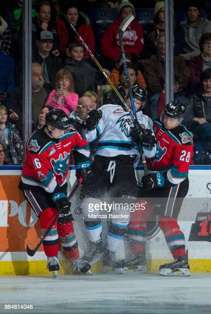 Kole Lind and Leif Mattson of the Kelowna Rockets checks a player of the Kootenay Ice into the boards during second period on December 2 2017 at...