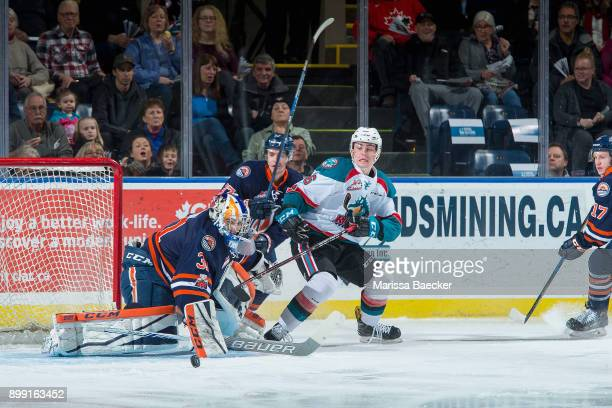 Kole Lind of the Kelowna Rockets is back checked by Joe Gatenby as Dylan Ferguson of the Kamloops Blazers makes a first period save on December 27...
