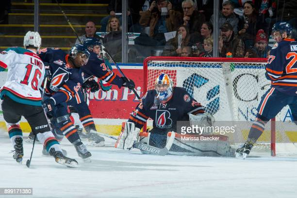 Kole Lind of the Kelowna Rockets tries to get past Jermaine Loewen as Dylan Ferguson of the Kamloops Blazers defends the net during second period on...
