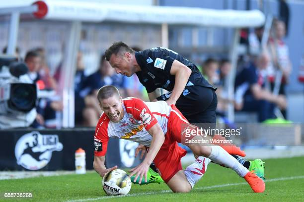 Kolja Pusch of Jahn Regensburg and Ivica Olic of 1860 Muenchen compete for the ball during the Second Bundesliga Playoff first leg match between Jahn...