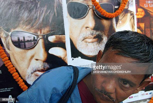 An Indian sweet vendor arranges his stall before garlanded promotional posters for Indian cinema icon Amitabh Bachchan's latest release Ek Ajnabi on...