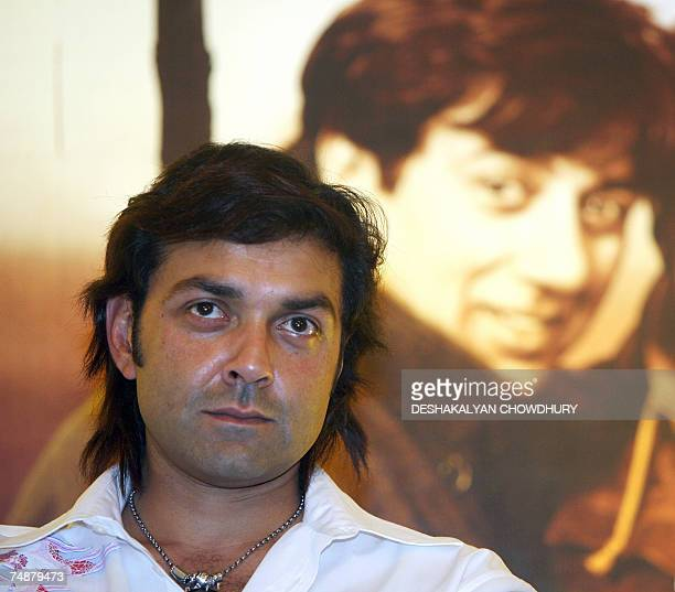 Indian actor Bobby Deol looks on as he sits front of a photograph of his actor brother Bobby Deol as they attends a promotional programme for a new...