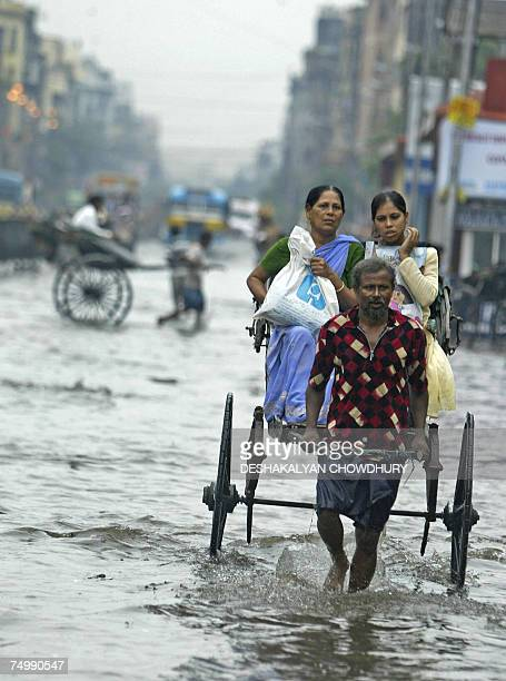 Indian commuters travel on a handpulled rickshaw to make their way through the flooded streets of Kolkata 03 July 2007 Heavy overnight rains threw...