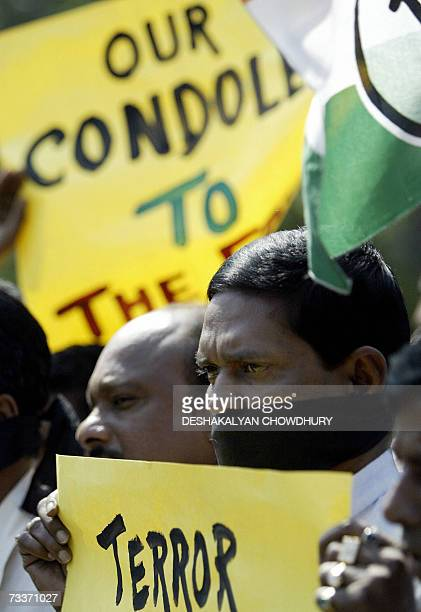 Indian Congress Party activists some with their mouths wrapped in black cloth carry bannersflags and placards while taking part in a condolence...