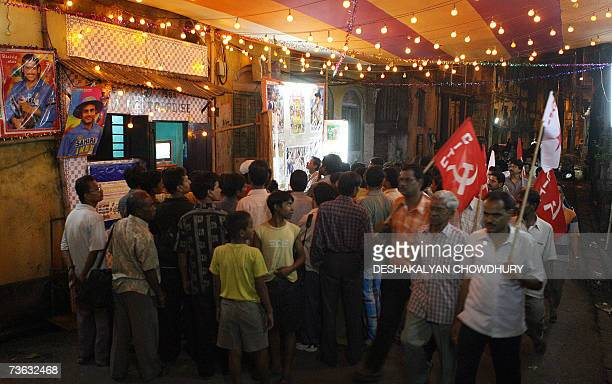 Indian cricket supporters watch the Indian cricket team in their World Cup 2007 match against Bermuda on a television set on a makeshift stage while...