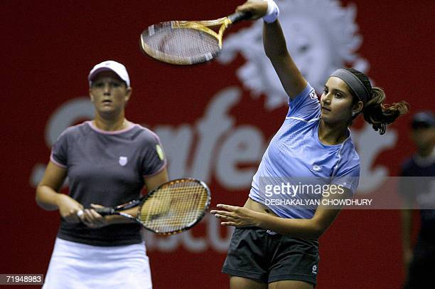 Indian tennis player Sania Mirza is watched by her doubles partner Liezel Huber of Russia as she serves during a prequarterfinal round match against...