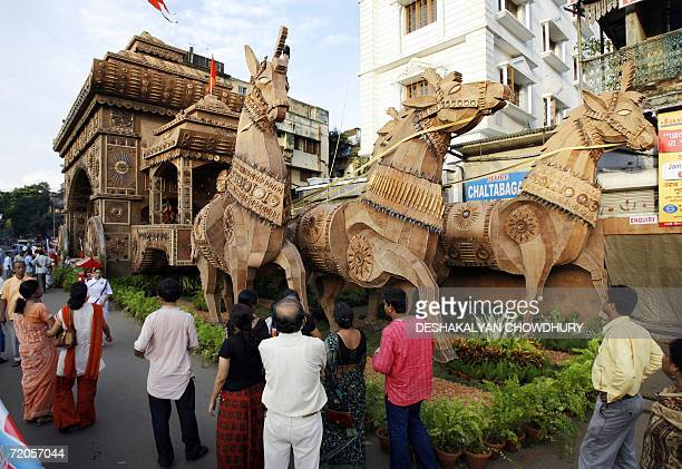 Indian visitors watch a makeshift Durga place of worship which is built as a wooden replica of a Rath Yatra in Kolkata 01 October 2006 The four day...