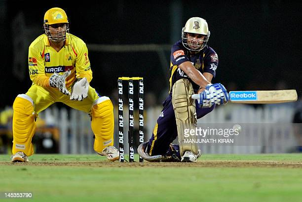 Kolkata Knight Riders batsman Manvinder Bisla plays a shot as Chennai Super Kings captain and wicketkeeper MS Dhoni looks on during the IPL Twenty20...