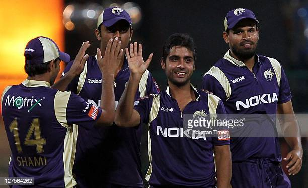 Kolkata Knight Riders bowler Iqbal Abdulla celebrates with teammates after claiming the wicket of RCB batsman Mohd Kaif, during the Champions League...