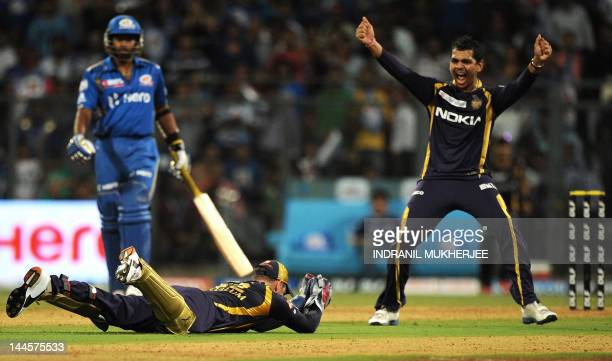 Kolkata Knight Riders cricketer Sunil Narine celebrates as teammate Brendon McCullum dives to take a catch of unseen Mumbai Indians batsman Rohit...