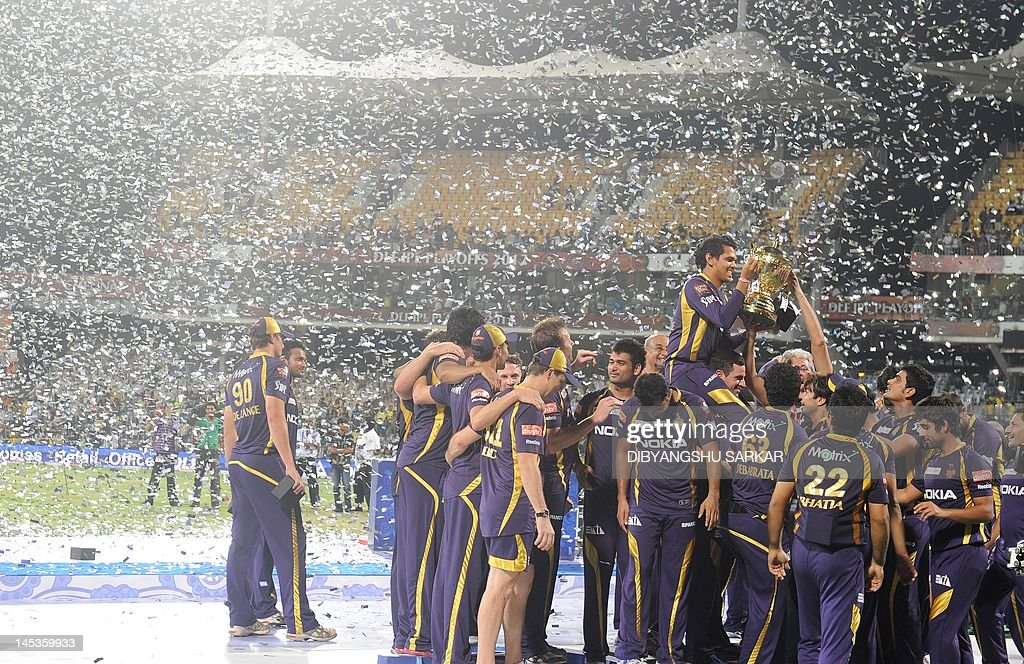 Kolkata Knight Riders cricketers, support staffs and officials celebrate with the DLF IPL trophy after winning the IPL Twenty20 cricket final match between Chennai Super Kings and Kolkata Knight Riders at the M.A.Chidambaram Stadium in Chennai on May 27, 2012. RESTRICTED TO EDITORIAL USE. MOBILE USE WITHIN NEWS PACKAGE. AFP PHOTO/Dibyangshu SARKAR