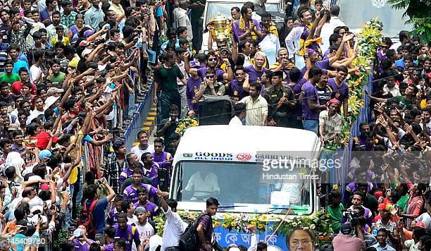 Kolkata Knight Riders' players ride on the back of a truck past a crowd of jubilant fans after winning the IPL during a victory parade on Ashutosh...