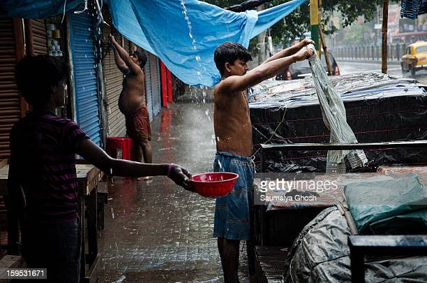 Kolkata street scene in a rainy day A dhobi is washing clothes and a boy is collecting water in a pot