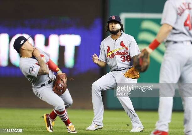 Kolten Wong and Jose Martinez of the St Louis Cardinals fail to catch a fly ball RBI single by Victor Robles of the Washington Nationals in the first...