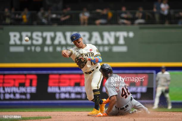Kolten Wong of the Milwaukee Brewers turns a double play in the sixth inning against Jeimer Candelario of the Detroit Tigers at American Family Field...