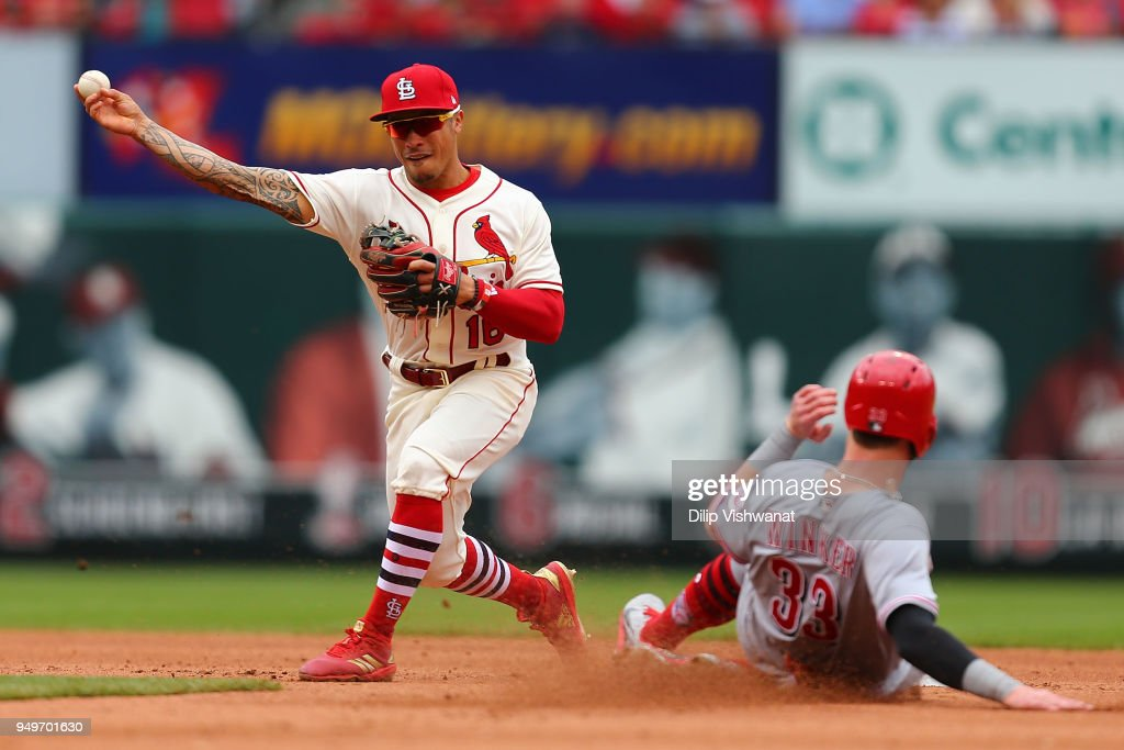 Kolten Wong #16 of the St. Louis Cardinals attempts to turn a double play against the Cincinnati Reds in the fifth inning at Busch Stadium on April 21, 2018 in St. Louis, Missouri.