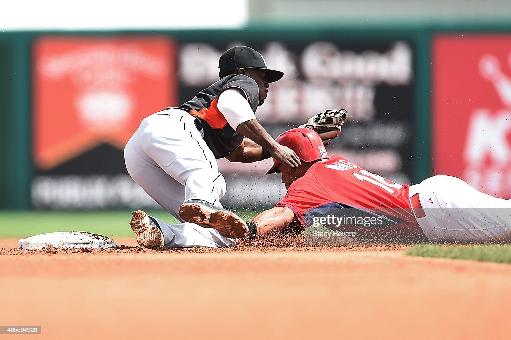 Kolten Wong #16 of the St. Louis Cardinals avoids a tag by Dee Gordon #9 of the Miami Marlins during the fourth inning of a spring training game at Roger Dean Stadium on March 8, 2015 in Jupiter, Florida.