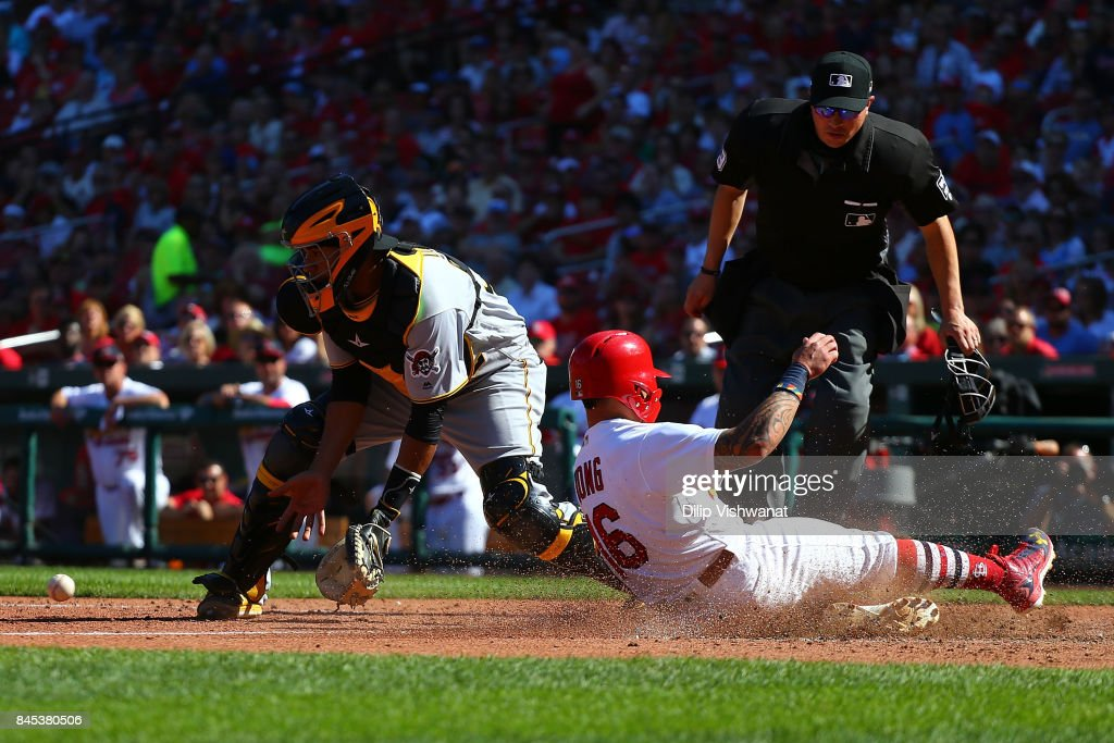 Kolten Wong #16 of the St. Louis Cardinals beats the throw to Elias Diaz #32 of the Pittsburgh Pirates to score a run in the seventh inning at Busch Stadium on September 10, 2017 in St. Louis, Missouri.