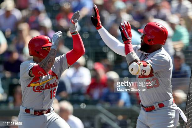 Kolten Wong of the St Louis Cardinals celebrates with Marcell Ozuna after hitting a home run in the first inning against the Colorado Rockies at...