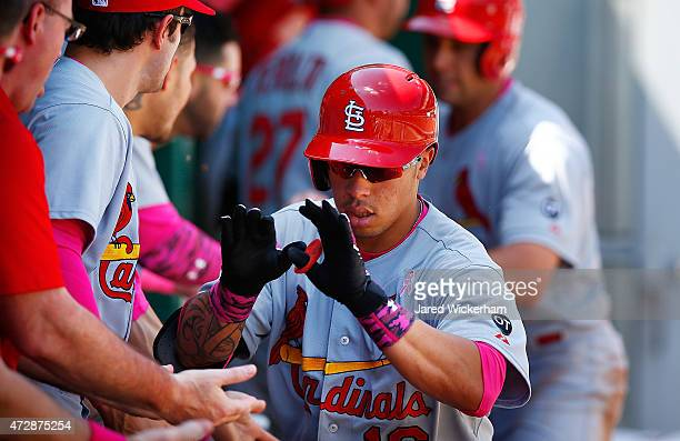 Kolten Wong of the St Louis Cardinals is congratulated by his teammates in the dugout after hitting a tworun home run in the sixth inning against the...