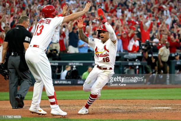 Kolten Wong of the St. Louis Cardinals is congratulated by his teammate Matt Carpenter after he comes home to score the game winning run on a...