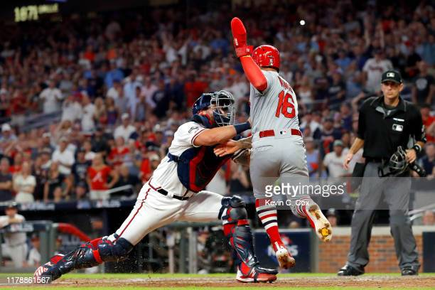 Kolten Wong of the St Louis Cardinals is tagged out at home plate by Francisco Cervelli of the Atlanta Braves in an attempt to score from first base...