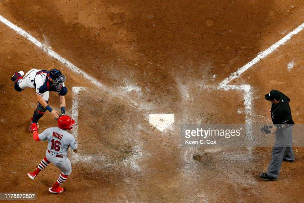 Kolten Wong of the St. Louis Cardinals is tagged out at home plate by Francisco Cervelli of the Atlanta Braves in an attempt to score from first base...