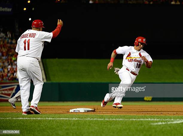 Kolten Wong of the St Louis Cardinals is waved home by third base coach Jose Oquendo during the fifth inning against the Arizona Diamondbacks at...