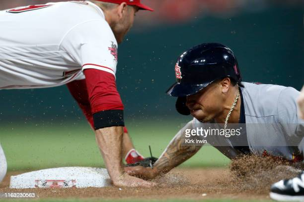 Kolten Wong of the St Louis Cardinals safely slides under the tag of Joey Votto of the Cincinnati Reds at first base during the game at Great...