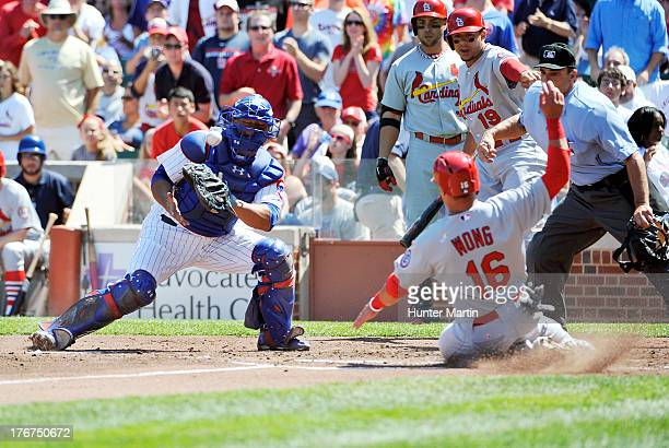 Kolten Wong of the St Louis Cardinals scores a run as Welington Castillo of the Chicago Cubs tries to make a tag during the second inning on August...