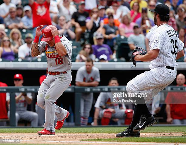 Kolten Wong of the St Louis Cardinals scores on a wild pitch and protects himself as pitcher Chad Bettis of the Colorado Rockies covers the plate and...