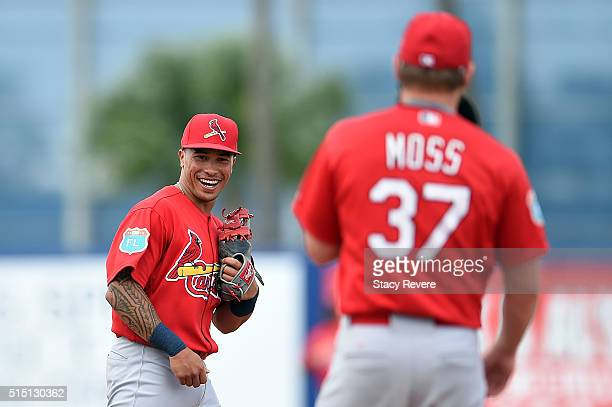 Kolten Wong of the St Louis Cardinals shares a laugh with Brandon Moss during the third inning of a spring training game against the New York Mets at...