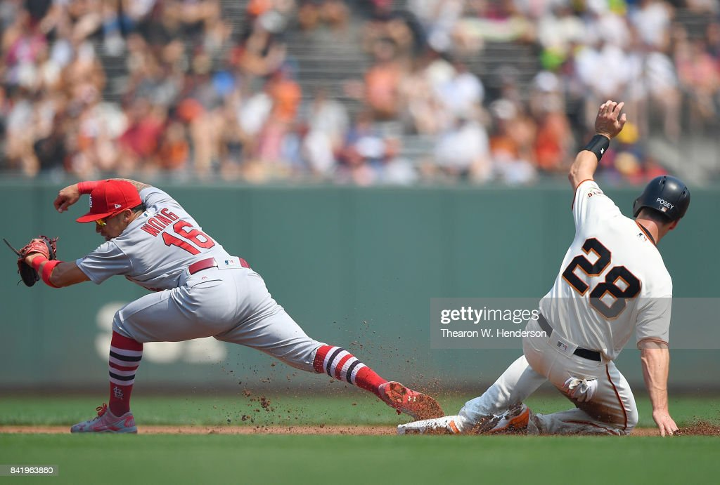 Kolten Wong #16 of the St. Louis Cardinals stretches at second base to get the put out on Buster Posey #28 of the San Francisco Giants in the bottom of the first inning at AT&T Park on September 2, 2017 in San Francisco, California.