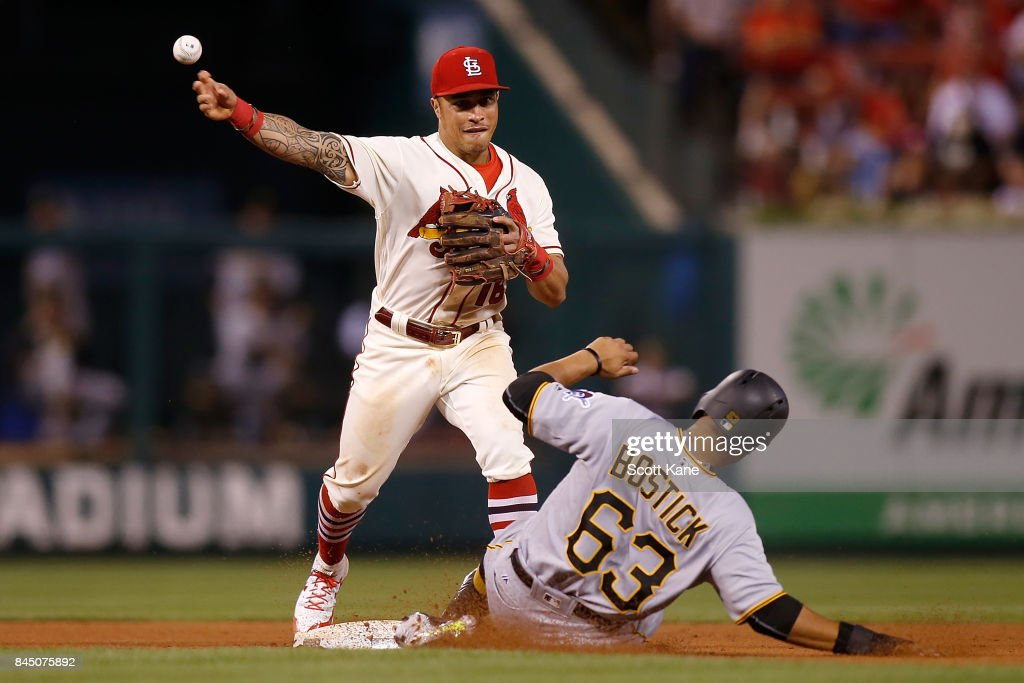 Kolten Wong #16 of the St. Louis Cardinals turns a double play over Chris Bostick #63 of the Pittsburgh Pirates during the eighth inning at Busch Stadium on September 9, 2017 in St. Louis, Missouri.