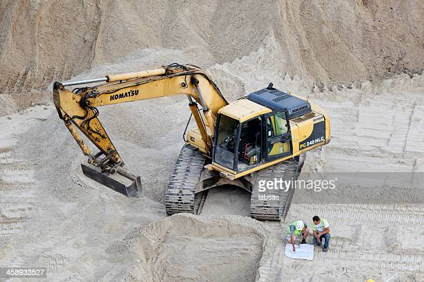 komatsu excavator and two construction workers on building site. - komatsu stock pictures, royalty-free photos & images