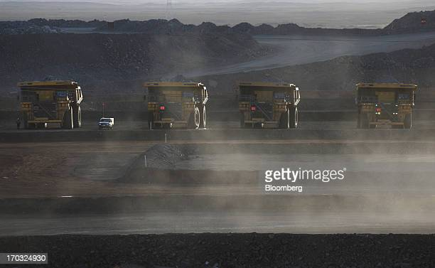 Komatsu Ltd dump trucks sit at the open pit of the Oyu Tolgoi coppergold mine jointly owned by Rio Tinto Group's unit Turquoise Hill Resources Ltd...