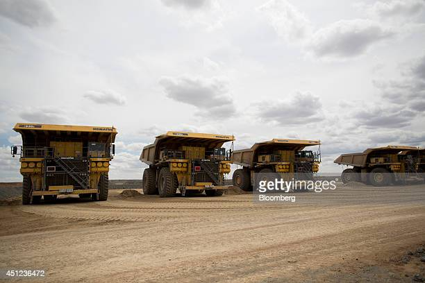 Komatsu Ltd. Dump trucks sit parked outside an open pit at the Oyu Tolgoi copper-gold mine, jointly owned by Rio Tinto Group's Turquoise Hill...
