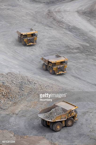 Komatsu Ltd. Dump trucks wait to be loaded with raw ore inside an open pit at the Oyu Tolgoi copper-gold mine, jointly owned by Rio Tinto Group's...