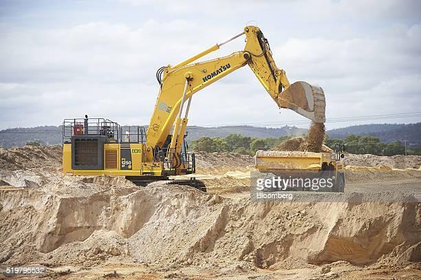 A Komatsu Ltd excavator loads sand into a dump truck at the MZI Resources Ltd Keysbrook mineral sands mine in Keysbrook near Perth Australia on...