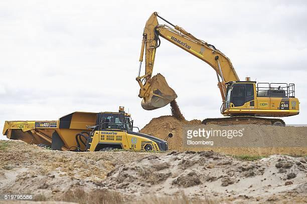 A Komatsu Ltd excavator moves sand near a dump truck in a pit at the the MZI Resources Ltd Keysbrook mineral sands mine in Keysbrook near Perth...
