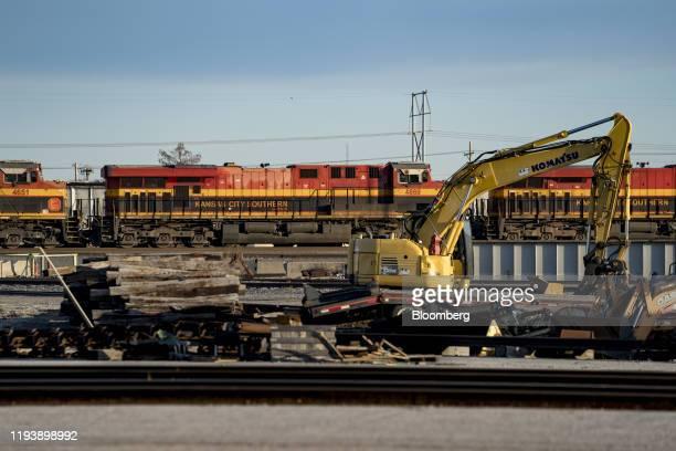 Komatsu Ltd. Excavator sits idle in front of a Kansas City Southern Railway locomotive parked at Knoche Yard in Kansas City, Missouri, U.S., on...
